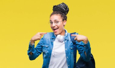 Young braided hair african american student girl wearing backpack over isolated background looking confident with smile on face, pointing oneself with fingers proud and happy.