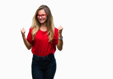 Young beautiful blonde woman wearing glasses over isolated background very happy and excited doing winner gesture with arms raised, smiling and screaming for success. Celebration concept.