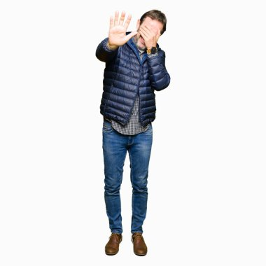 Middle age handsome man wearing winter coat covering eyes with hands and doing stop gesture with sad and fear expression. Embarrassed and negative concept.