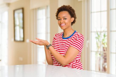 Young beautiful african american woman at home Pointing to the side with hand and open palm, presenting ad smiling happy and confident