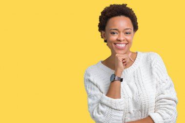 Beautiful young african american woman wearing sweater over isolated background looking confident at the camera with smile with crossed arms and hand raised on chin. Thinking positive.