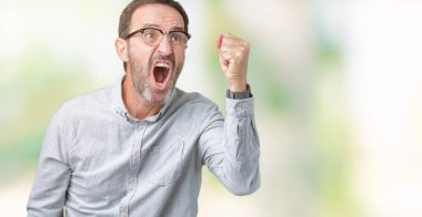 Handsome middle age elegant senior man wearing glasses over isolated background angry and mad raising fist frustrated and furious while shouting with anger. Rage and aggressive concept.