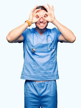 Handsome doctor man wearing medical uniform over isolated background doing ok gesture like binoculars sticking tongue out, eyes looking through fingers. Crazy expression.