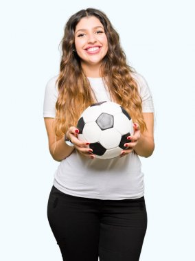 Young adult woman holding soccer football ball with a happy face standing and smiling with a confident smile showing teeth