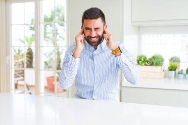 Handsome hispanic business man covering ears with fingers with annoyed expression for the noise of loud music. Deaf concept.