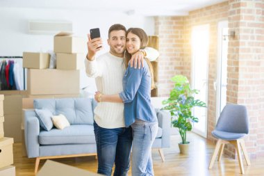 Beautiful couple taking a selfie photo using smartphone at new apartment, smiling happy for new house