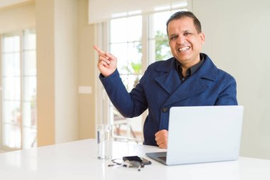 Middle age business man working using laptop with a big smile on face, pointing with hand and finger to the side looking at the camera.