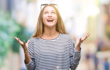 Young beautiful blonde woman wearing sunglasses over isolated background crazy and mad shouting and yelling with aggressive expression and arms raised. Frustration concept.