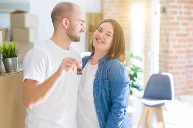 Young couple smiling very happy showing keys of new home, moving