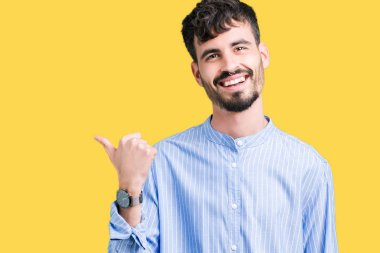 Young handsome business man over isolated background smiling with happy face looking and pointing to the side with thumb up.