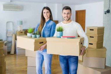 Young couple moving to a new home, smiling happy holding cardboard boxes at new apartment