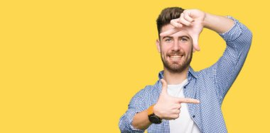 Young handsome blond man wearing casual shirt smiling making frame with hands and fingers with happy face. Creativity and photography concept.