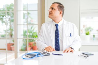 Middle age doctor man wearing medical coat at the clinic looking to side, relax profile pose with natural face with confident smile.