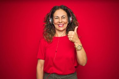 Middle age senior woman wearing headphones listening to music over red isolated background doing happy thumbs up gesture with hand. Approving expression looking at the camera with showing success.