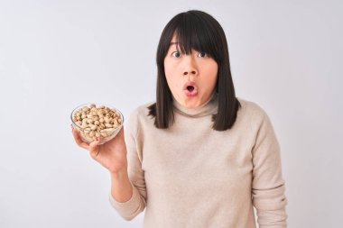 Young beautiful Chinese woman holding bowl with pistachios over isolated white background scared in shock with a surprise face, afraid and excited with fear expression