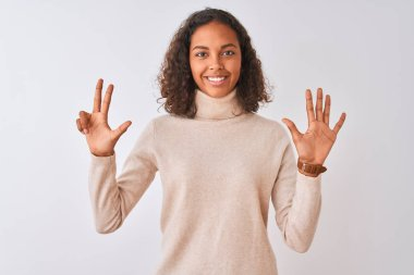 Young brazilian woman wearing turtleneck sweater standing over isolated white background showing and pointing up with fingers number eight while smiling confident and happy.