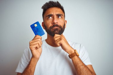 Young indian customer man holding credit card standing over isolated white background serious face thinking about question, very confused idea