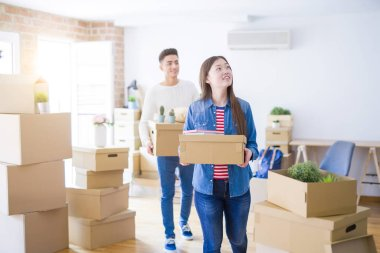 Beautiful young asian couple looking happy holding cardboard boxes, smiling excited moving to a new home