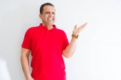 Middle age man wearing red t-shirt over white wall smiling cheerful presenting and pointing with palm of hand looking at the camera.
