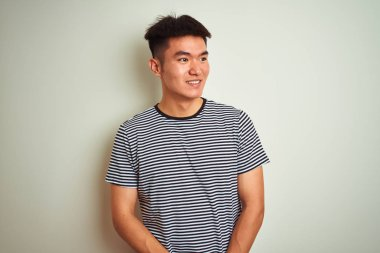 Young asian chinese man wearing striped t-shirt standing over isolated white background looking away to side with smile on face, natural expression. Laughing confident.