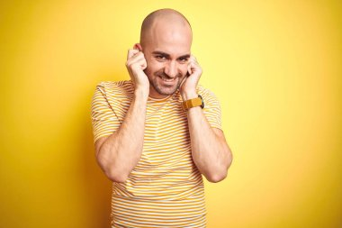 Young bald man with beard wearing casual striped t-shirt over yellow isolated background covering ears with fingers with annoyed expression for the noise of loud music. Deaf concept.
