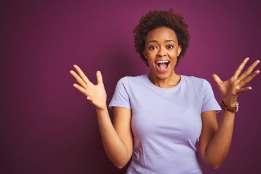 Young beautiful african american woman with afro hair over isolated purple background celebrating crazy and amazed for success with arms raised and open eyes screaming excited. Winner concept