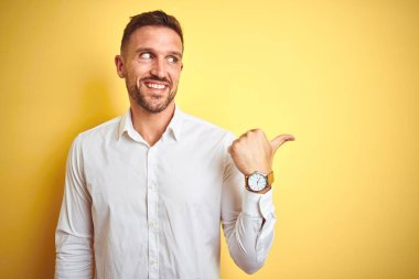 Young handsome man wearing elegant white shirt over yellow isolated background smiling with happy face looking and pointing to the side with thumb up.