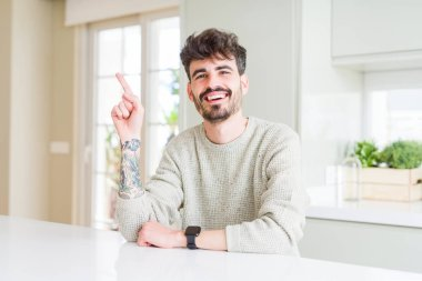 Young man wearing casual sweater sitting on white table with a big smile on face, pointing with hand and finger to the side looking at the camera.
