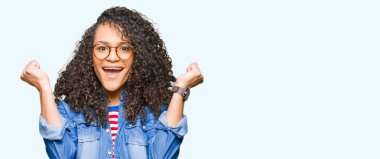 Young beautiful woman with curly hair wearing glasses celebrating surprised and amazed for success with arms raised and open eyes. Winner concept.