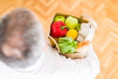 Overhead angle of senior man holding bag full of fresh groceries