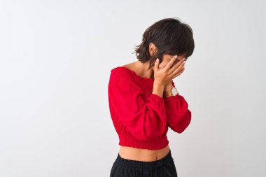Young beautiful woman wearing red summer t-shirt standing over isolated white background with sad expression covering face with hands while crying. Depression concept.