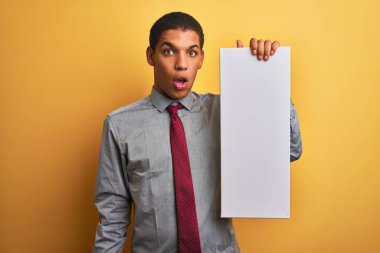 Young handsome arab businessman holding banner standing over isolated yellow background scared in shock with a surprise face, afraid and excited with fear expression