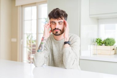 Young man wearing casual sweater sitting on white table with hand on head for pain in head because stress. Suffering migraine.