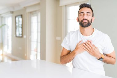 Handsome hispanic man casual white t-shirt at home smiling with hands on chest with closed eyes and grateful gesture on face. Health concept.