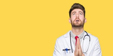 Young handsome doctor man wearing medical coat begging and praying with hands together with hope expression on face very emotional and worried. Asking for forgiveness. Religion concept.