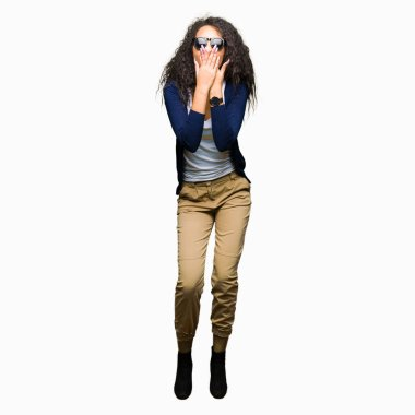 Young beautiful girl with curly hair wearing fashion sunglasses shocked covering mouth with hands for mistake. Secret concept.