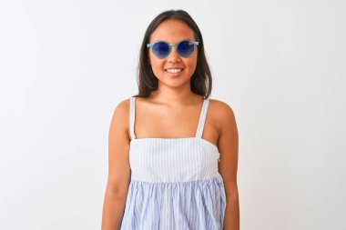 Young chinese woman wearing striped dress and sunglasses over isolated white background with a happy and cool smile on face. Lucky person.