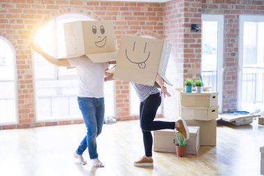 Middle age senior couple moving to a new home with boxes around with a big smile on face, pointing with hand and finger to the side looking at the camera.