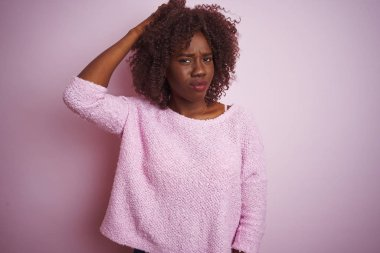 Young african afro woman wearing sweater standing over isolated pink background confuse and wonder about question. Uncertain with doubt, thinking with hand on head. Pensive concept.