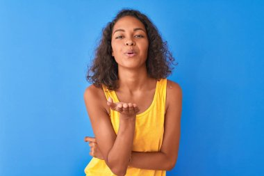 Young brazilian woman wearing yellow t-shirt standing over isolated blue background looking at the camera blowing a kiss with hand on air being lovely and sexy. Love expression.