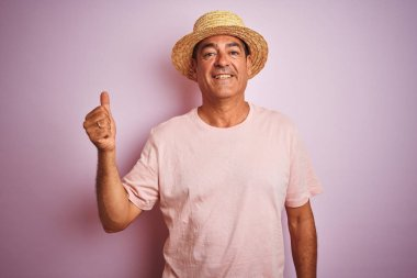 Handsome middle age man wearing summer hat standing over isolated pink background doing happy thumbs up gesture with hand. Approving expression looking at the camera with showing success.