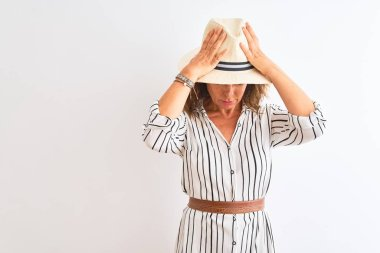 Middle age businesswoman wearing striped dress and hat over isolated white background suffering from headache desperate and stressed because pain and migraine. Hands on head.