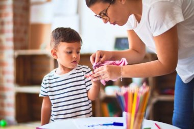 Beautiful teacher and toddler boy drawing draw using colored pencils at kindergarten