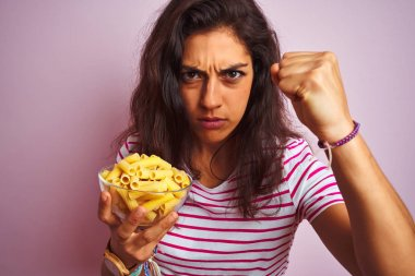 Young beautiful woman holding bowl with dry macaroni pasta over isolated pink background annoyed and frustrated shouting with anger, crazy and yelling with raised hand, anger concept