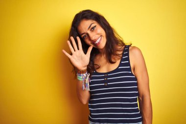 Young beautiful woman wearing striped t-shirt standing over isolated yellow background showing and pointing up with fingers number five while smiling confident and happy.