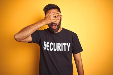 Arab indian hispanic safeguard man wearing security uniform over isolated yellow background peeking in shock covering face and eyes with hand, looking through fingers with embarrassed expression.