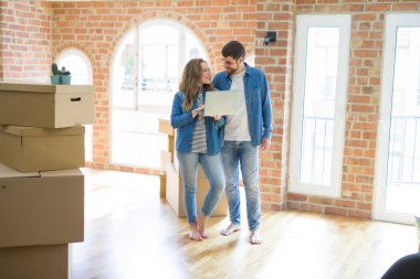 Young couple using computer laptop standing on a room around cardboard boxes, happy for moving to a new apartment