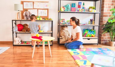 Beautiful teacher and toddler boy standing at kindergarten with lots of toys