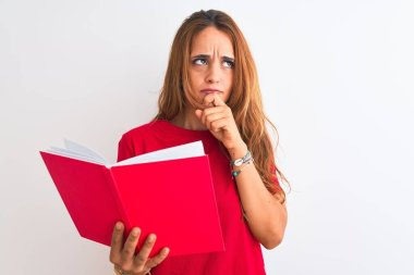 Young beautiful redhead woman reading a red book over isolated background serious face thinking about question, very confused idea