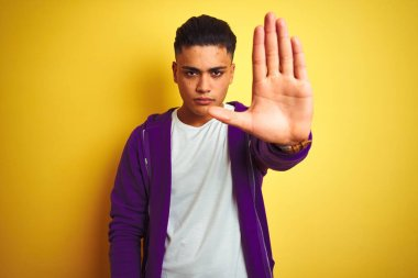 Young brazilian man wearing purple sweatshirt standing over isolated yellow background doing stop sing with palm of the hand. Warning expression with negative and serious gesture on the face.